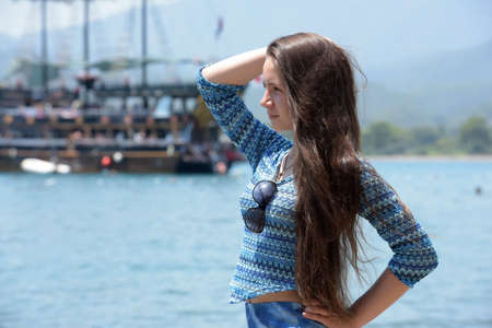 fair haired: Beautiful young girl on a background of a sailing boat on the sea in water.