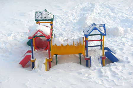 ander: A childrens playground and a slide in the snow.