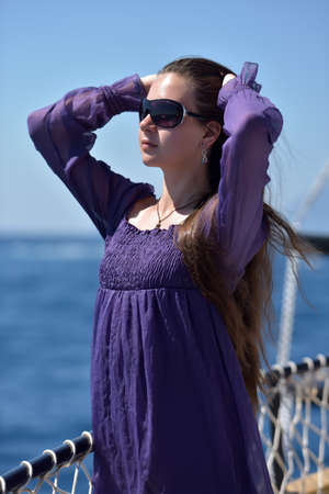 Girl with long hair in a purple dress on a ship on the sea background.