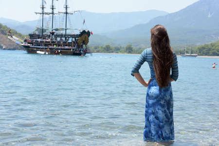 mujer mirando el horizonte: hermosa joven sobre un fondo de un barco de vela en el mar en agua.