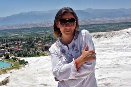 Woman in white on a background of calcium Pamukkale travertine.