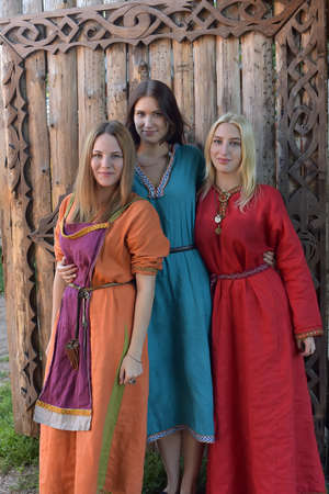 Three girls dressed in historical medieval reconstruction Varangian manor, Russia. Editorial