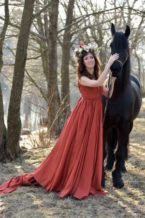 Brunette woman in a red dress with a wreath of flowers on her head and a black horse. Imagens
