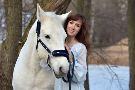 Charming brunette in pale blue dress with a white horse in the early spring.