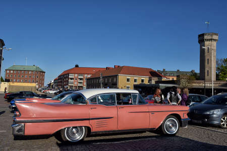 Classic car painted in the scheme of a pink cadillac. Symbol in popular culture. .