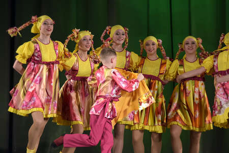 synchronously: Childrens theatrical performance of dance group in national costume, Russia, St. Petersburg.
