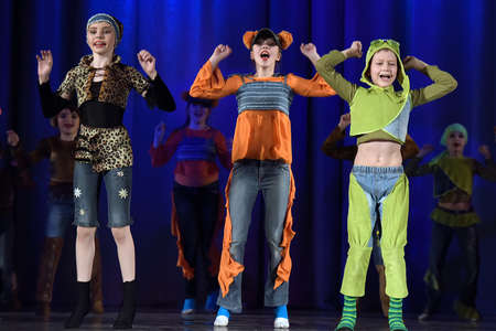christmas frog: Children dancing on the stage in animal costumes Editorial