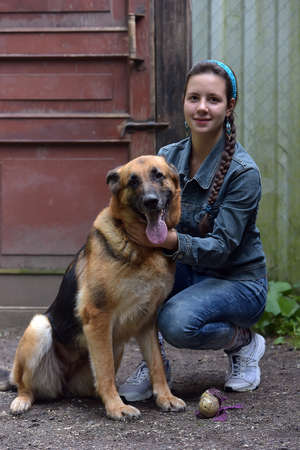 a girl in a denim suit with a sheepdog