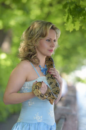 Blond woman in elegant dress with a python in hands.