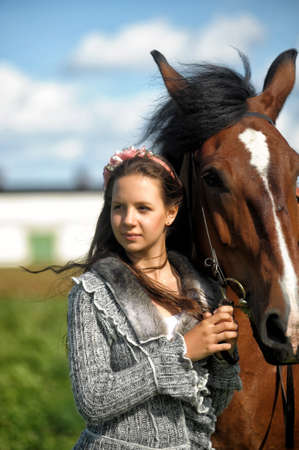 Beautiful young teen girl with the brown horse.