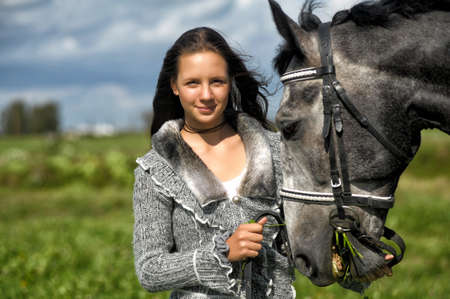 Beautiful young teen girl with the grey horse. Stock Photo