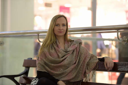 Woman in beige Wraps sitting on a bench.
