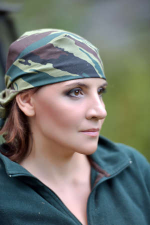 Woman wearing camouflage bandana against the backdrop of UAZ Stock Photo