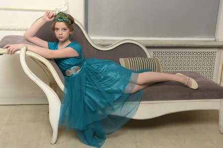 The girl child in the glamorous dress aqua on the couch