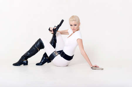Sexy blonde with a gun in hand. photo