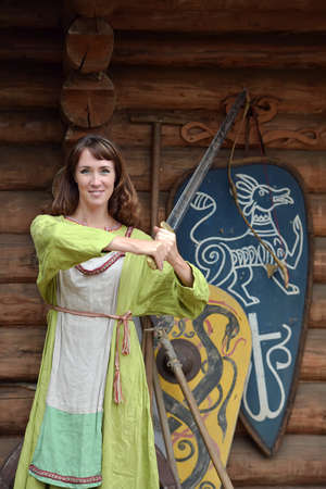 Woman in a green dress with a sword in hand.