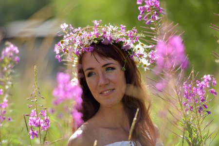 Brunette in white in summer tea willow field with wreath on head photo