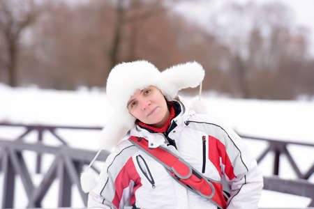 Woman in a sports jacket and a white fur hat photo