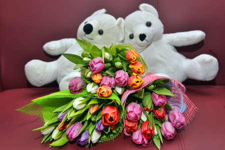 White teddy bears and bouquets of tulips