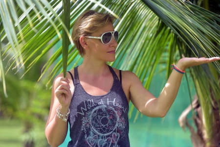 Blonde woman with short hair next to palm leaves photo