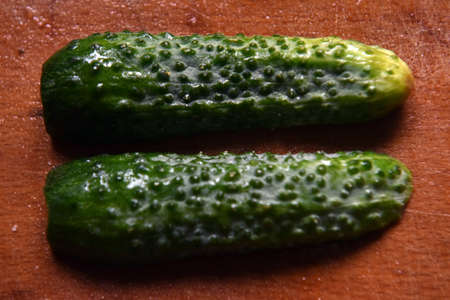 Two halves of a cucumber on a wooden background