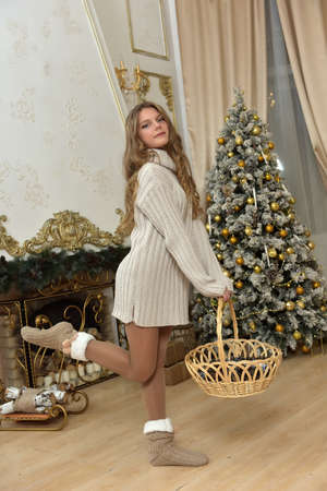 girl teenager in a sweater with a wicker basket at a Christmas tree