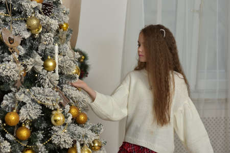 girl in a white sweater with cat ears near the Christmas tree Stockfoto