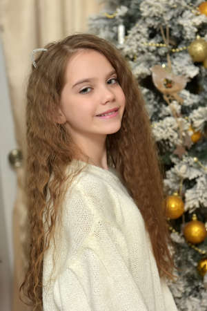 girl in a white sweater with cat ears near the Christmas tree