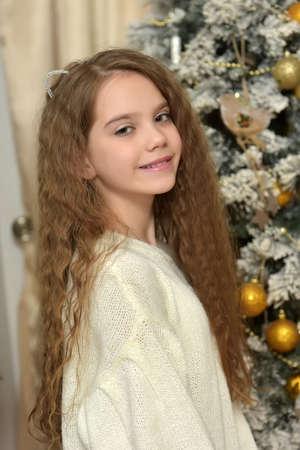 meisje in een witte trui met kat oren in de buurt van de kerstboom