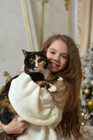 girl with long hair with a cat in her arms near the Christmas tree