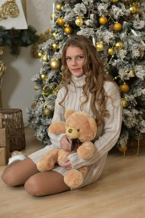 girl teenager in a knitted sweater with a teddy bear at the Christmas tree on the floor at Christmas