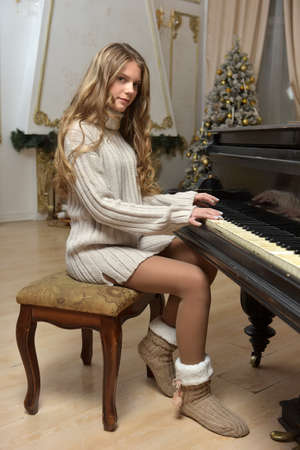 girl teenager in a knitted sweater at a piano in Christmas