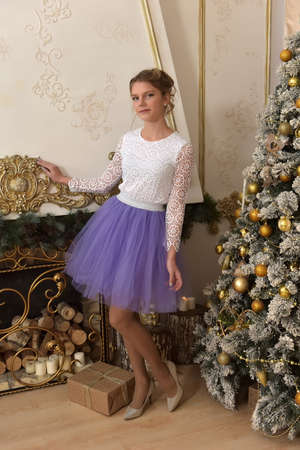 girl teenager in white blouse and lilac skirt at christmas tree
