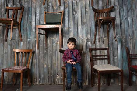 sad boy in checkered shirt sitting on chair