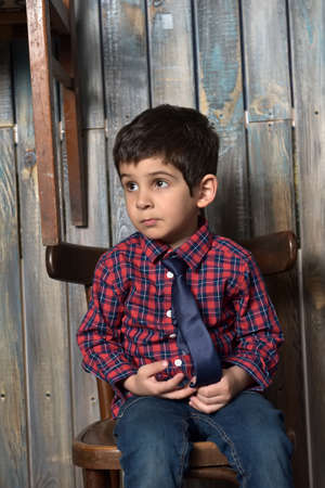 sad boy in checkered shirt sitting on chair Banco de Imagens - 94320488