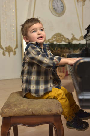 cute little boy, sitting on chair and playing on piano