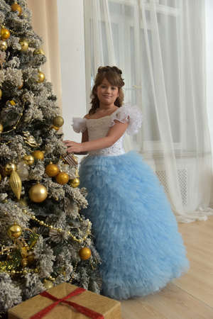 Young princess in white with blue elegant dress at Christmas tree at Christmas