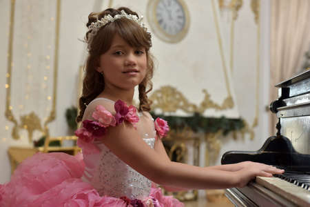 The young princess in white with a pink dress with a piano