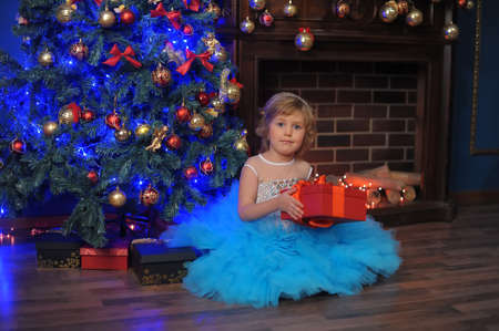 girl in white with blue dress in christmas with a gift