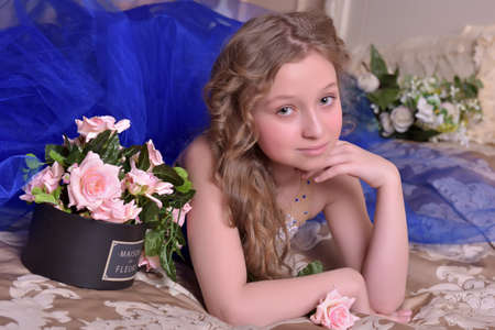 Young princess in a blue evening dress with roses . Beauty, blond.