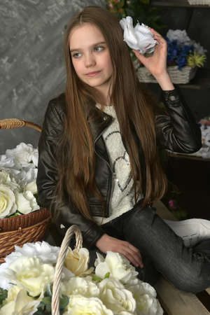 young girl in a black leather jacket is crouched among baskets with flowers Banque d'images - 97893864