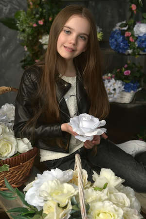 young girl in a black leather jacket is crouched among baskets with flowers Banque d'images - 97893871