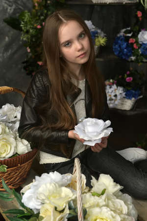 young girl in a black leather jacket is crouched among baskets with flowers Banque d'images - 97893870