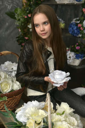 young girl in a black leather jacket is crouched among baskets with flowers Banque d'images - 97893867