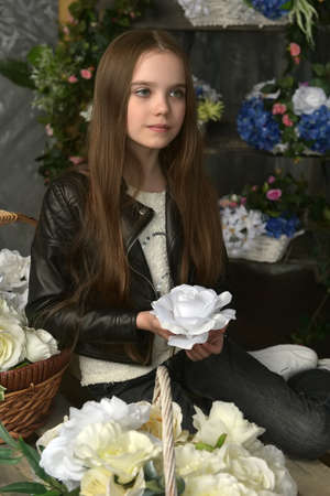 young girl in a black leather jacket is crouched among baskets with flowers Banque d'images - 96801209
