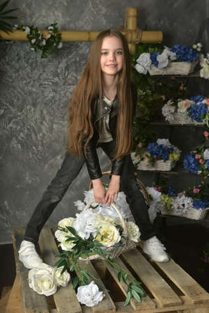 young girl in a black leather jacket is crouched among baskets with flowers