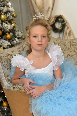 princess in white with blue elegant dress sits on an armchair in christmas