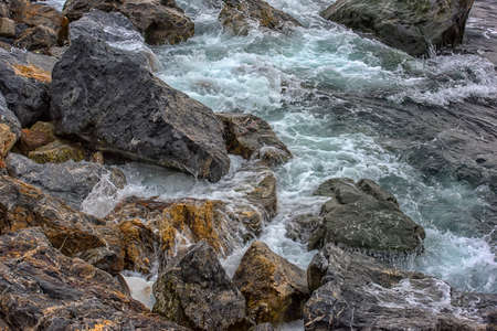 View from rock down on sea surf with wave splash and water running from stones back to sea Stockfoto