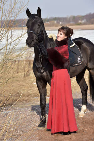 woman in vintage stylized suit with  horse