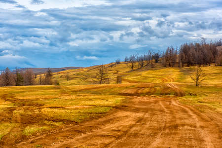 Track winding back roads in the mountains. Dirt road on Olkhon island in lake Baikal. For guide to Russia.